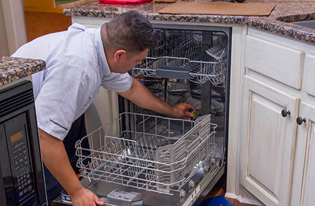 Technician looking inside a dishwasher to troubleshoot and diagnose the problem